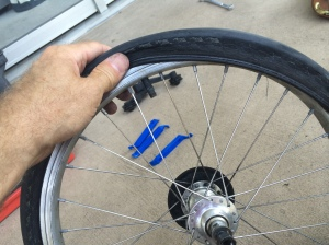 Easing the tire back onto the rim with my fingers only -- this is to avoid piercing it again with a tool.